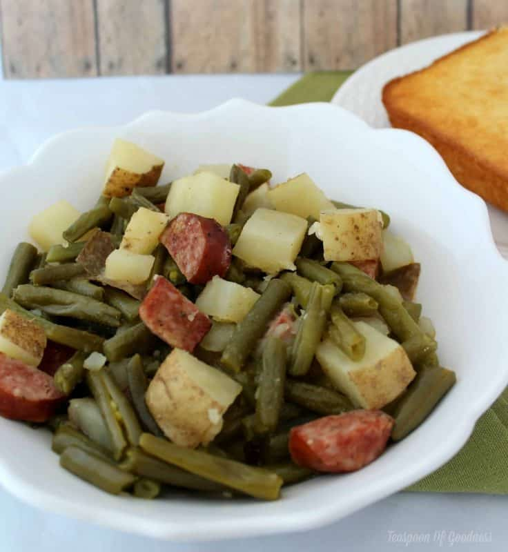 Green Beans, Sausage and potatoes cooked in a slow cooker in a white bowl.