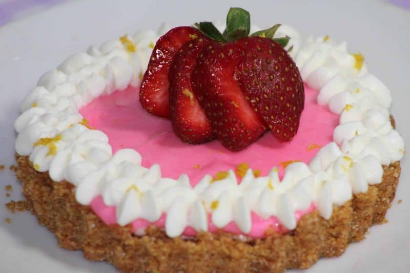 Mini No-Bake Berry Cheesecake with a graham cracker crust topped with strawberries and whip cream