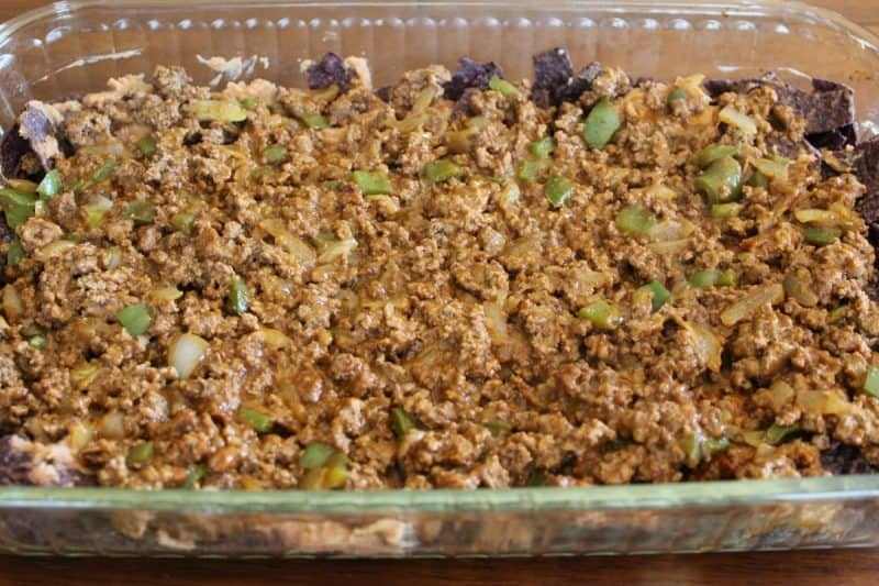 ground beef for layered taco salad in a cake pan