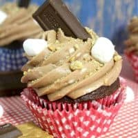 S'Mores Cupcake in a red cupcake liner with Hershey bar piece and mini marshmallows on top.