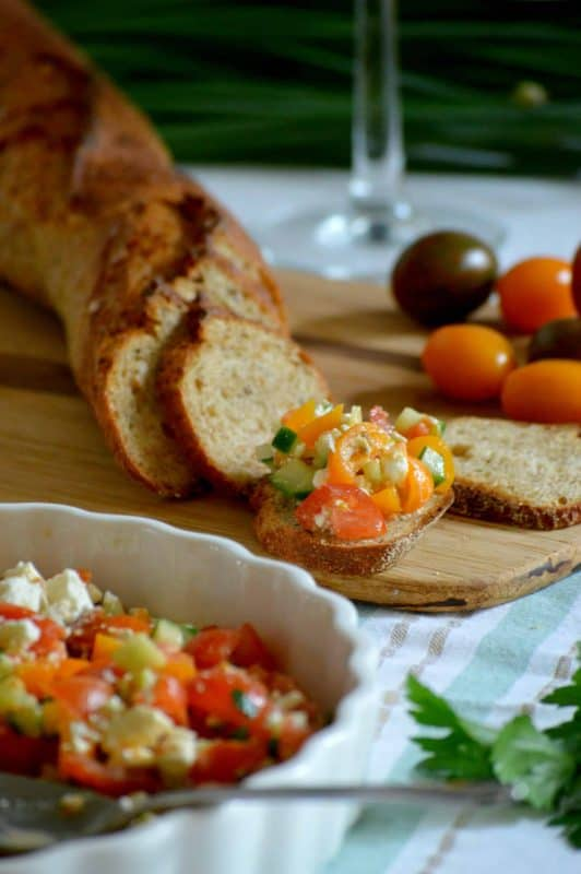Feta, Cucumber & Tomato Appetizer in a tart pan with a baguette in the background.