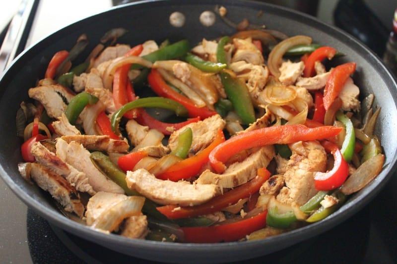 Easy Weeknight Chicken Fajitas sauteing in a pan.