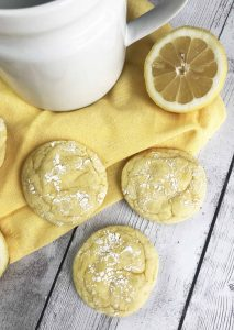 3 Lemon cookies with a lemon and sugar bowl in the background.