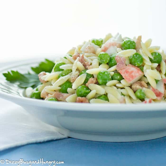 intimation crab, orzo pasta, peas and bacon combined to make a crab pasta salad in a serving bowl
