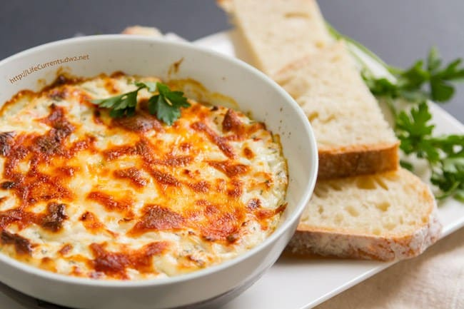 a cheesy hot crab dip made with imitation crab with a side of bread in a serving bowl