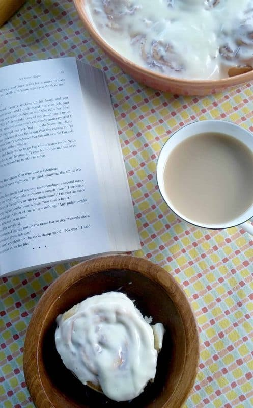 Cherry pineapple upside down cinnamon roll on a plate with a cup of coffee and a book.