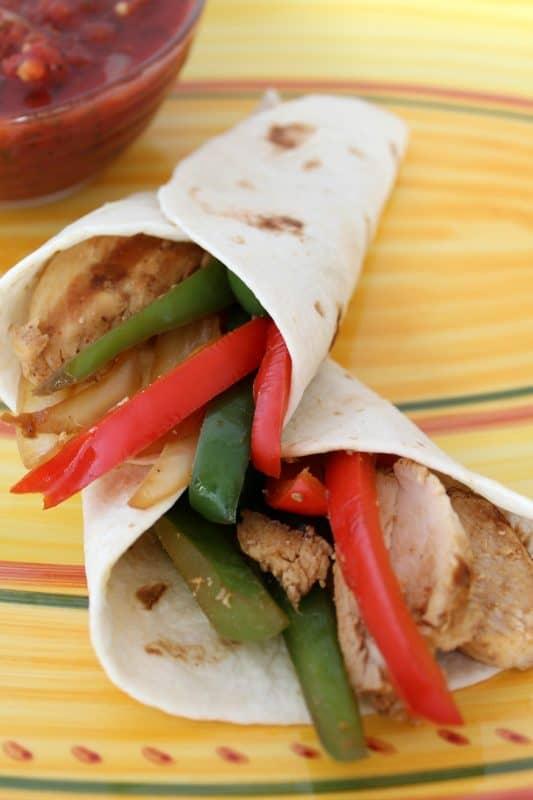 Easy Weeknight Chicken Fajitas in flour tortillas.