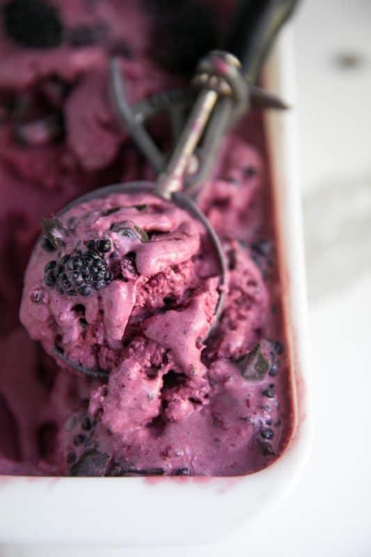No churn blackberry chocolate ice cream in an ice cream scoop.