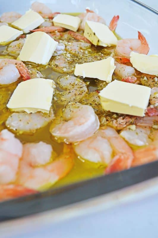 Baked shrimp scampi pasta ready to go in the oven with butter on top.