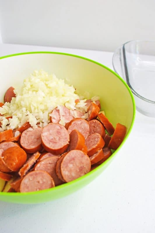 Sausage and potatoes with diced onions in a lime green bowl
