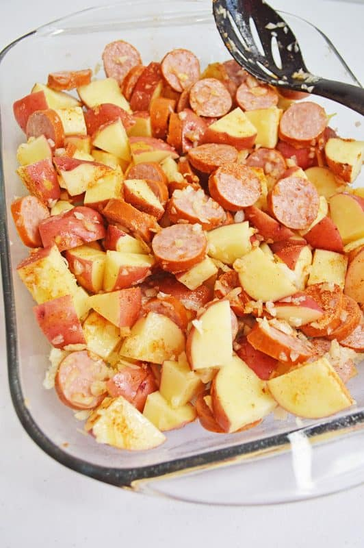 Sausage and potatoes with diced onions in a clear baking dish
