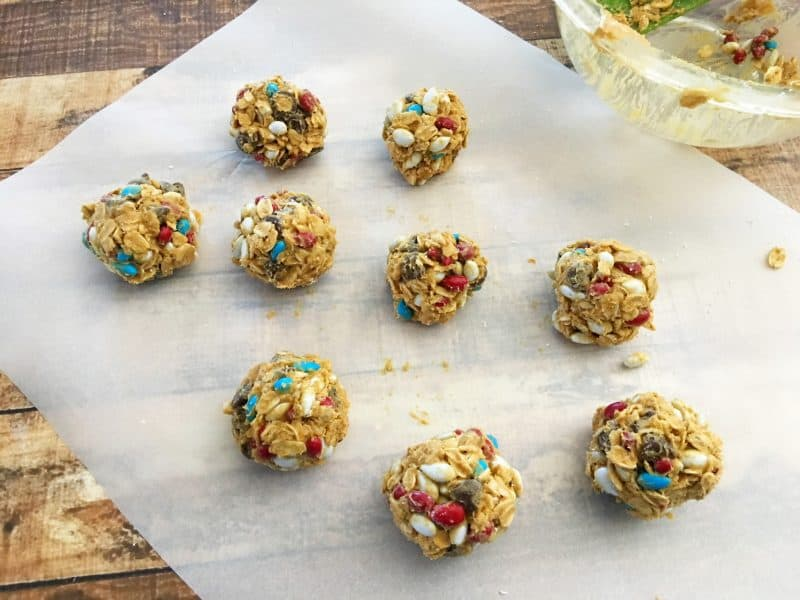 Chocolate chips, m&m's, oats and peanut butter in a bowl that will be made into no bake protein balls.