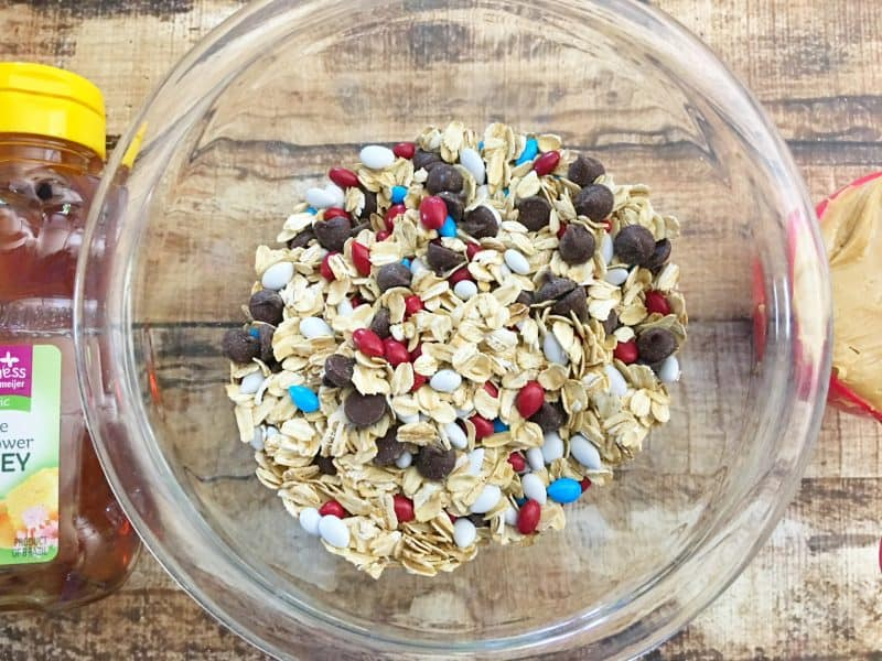 Chocolate chips, m&M's and oats in a bowl that will be made into no bake protein balls.