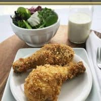Chicken Legs on a white plate with Salad in a white bowl and Dressing in a jar in the background