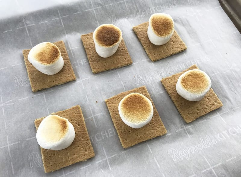 Graham crackers and marshmallows being prepped for Chocolate Chip Cookie S'mores.