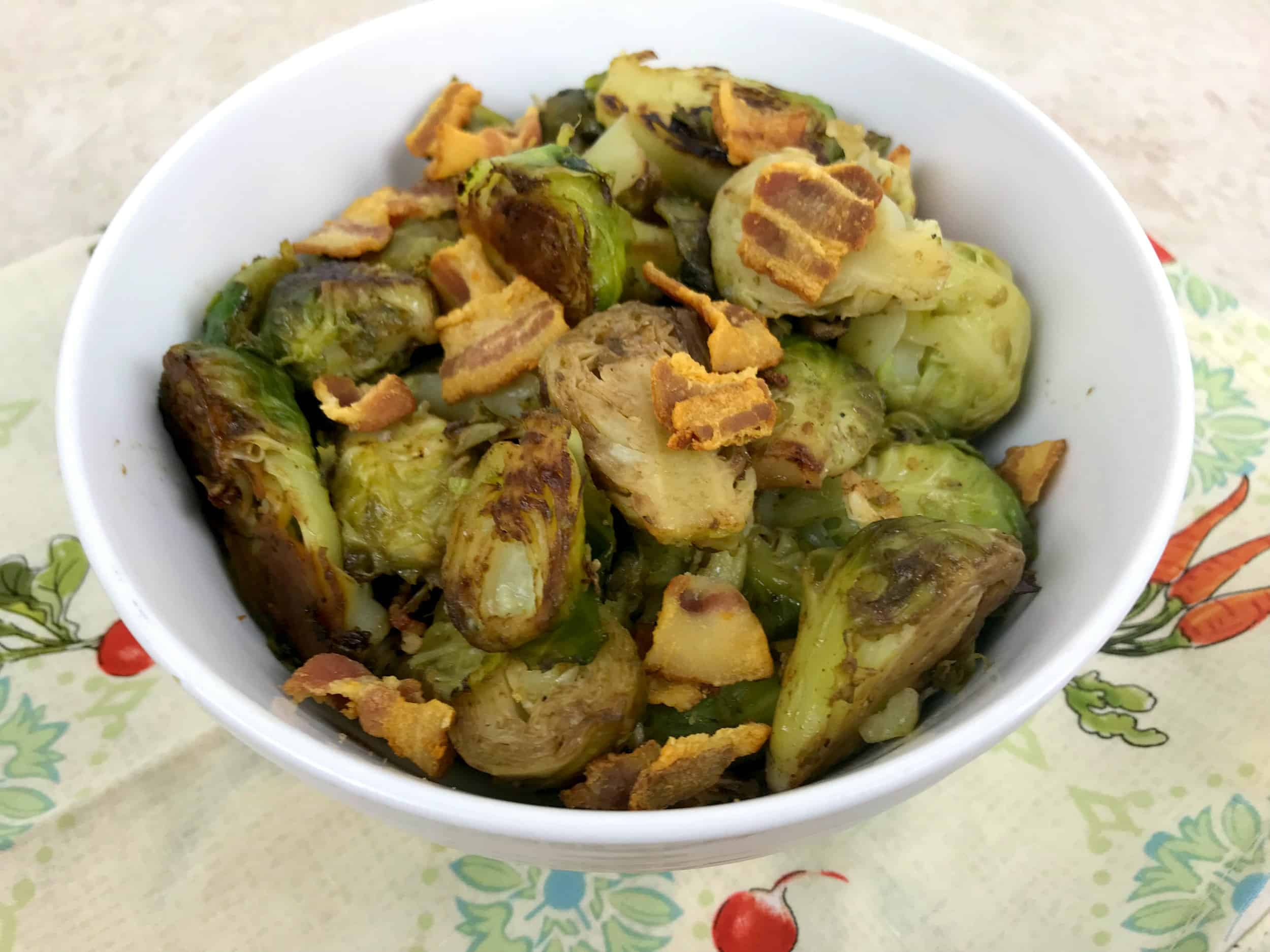Seared bacon and brussel sprouts in a white bowl.