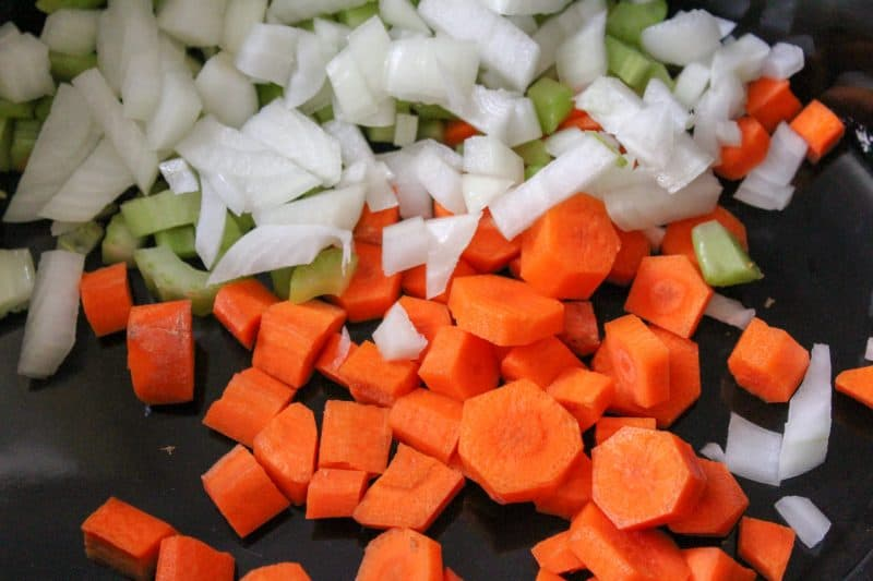 Diced carrots, onions and celery combined in a pan for a homemade beef stew recipe.