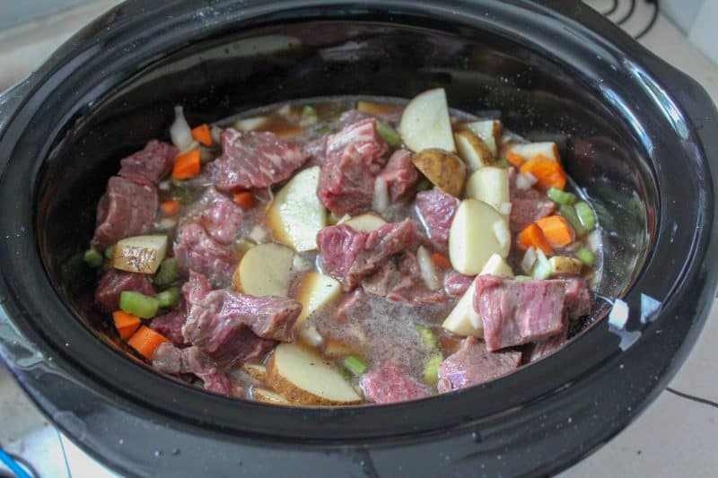 Diced meat and vegetables in a slow cooker for a homemade beef stew recipe.