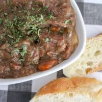 Slow cooker beef stew recipe in a white bowl with carrots, potatoes and bread in the background.