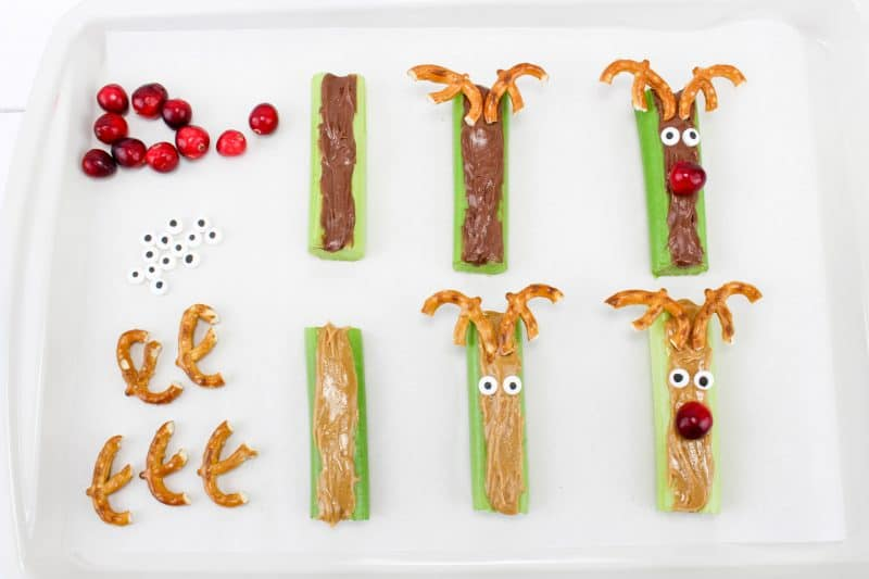 Nutella and peanut butter celery sticks with pretzels as horns, candy eyes and a cranberry for Rudolph's nose.