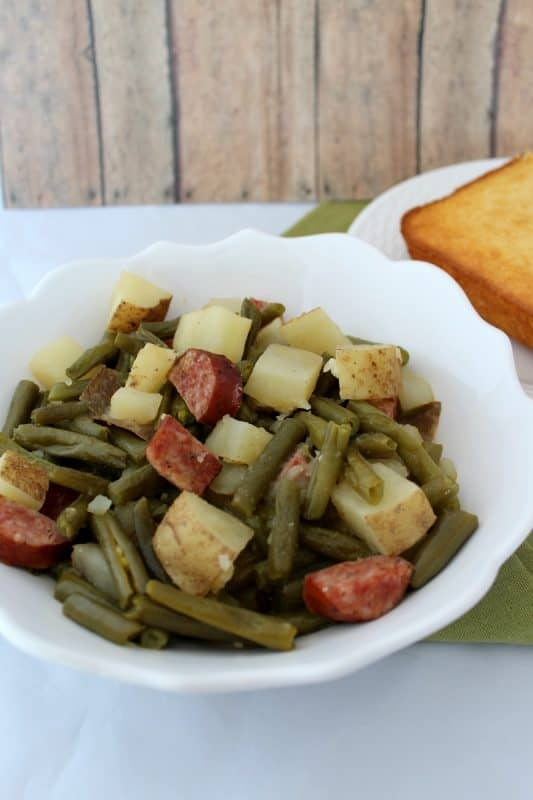 Smoked sausage and potatoes with green beans in a crock pot with chicken stock in a white bowl.