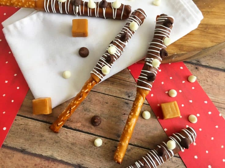 Caramel chocolate covered pretzel rods on a white cloth with a brown background.
