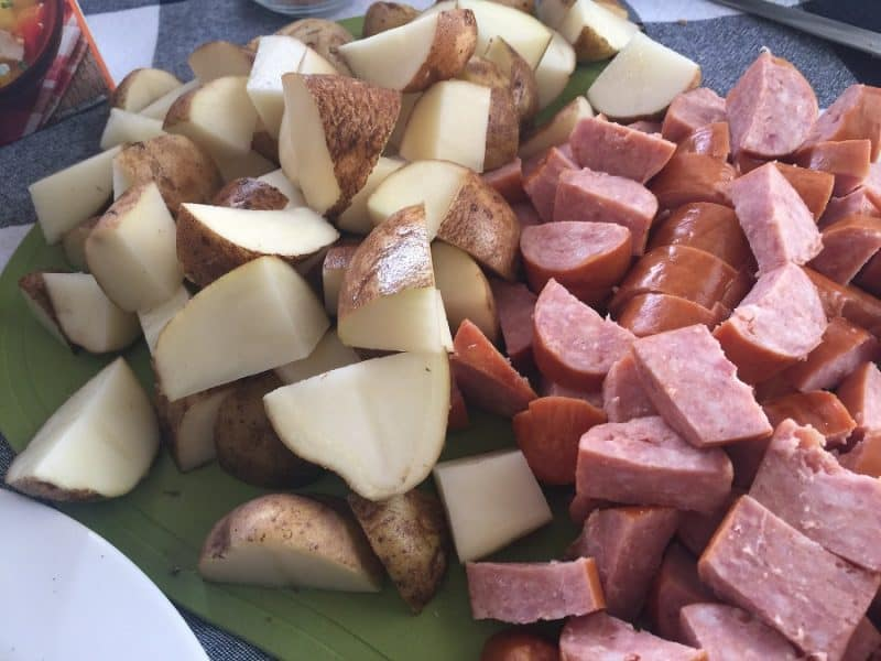 Diced potatoes and smoked sausage on a cutting board