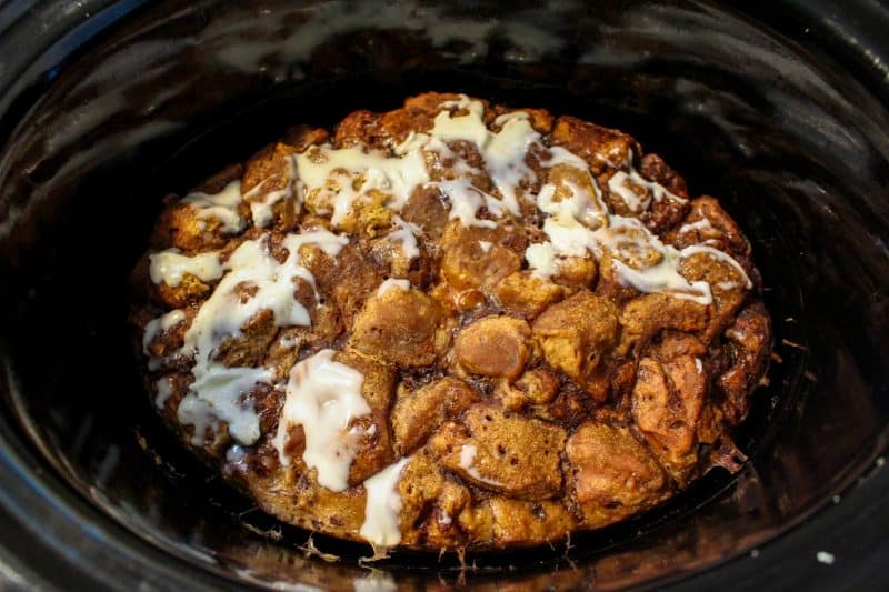 Cinnamon roll icing being poured over the top of a crockpot cinnamon roll casserole.