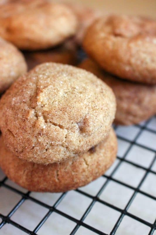 Maple Snickerdoodle cookies stacked on a cooling rack.