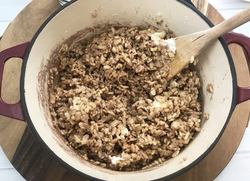 Hot cocoa rice krispies being mixed with a wooden spoon in a pan.