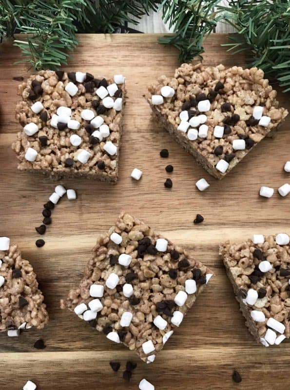 Hot cocoa rice krispie treats with mini chocolate chips and mini marshmallows on a wooden background.