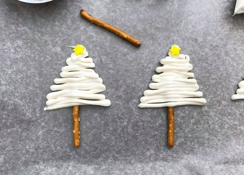 Pretzels drizzled with white chocolate that are decorated like Christmas Trees with sprinkles and a star on top.