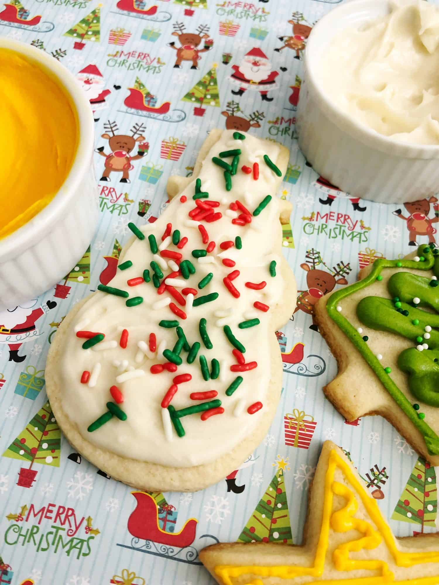A snowman sugar cookie decorated in white with sprinkles using our families favorite sugar cookie frosting.