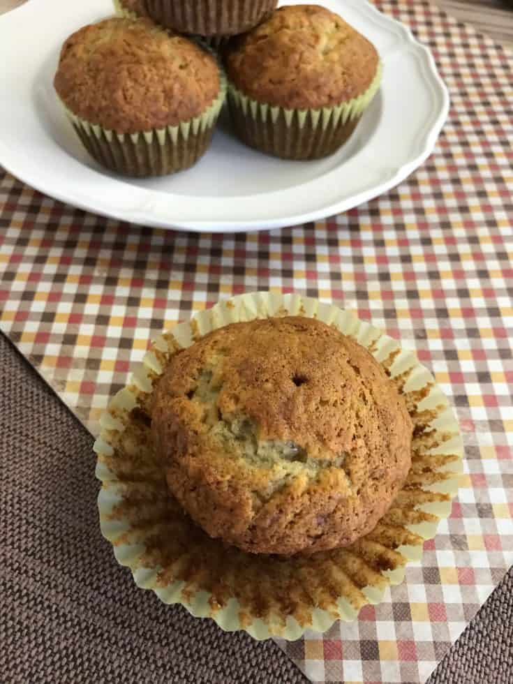 Moist banana muffins on a white plate setting on top of a checkered napkin.