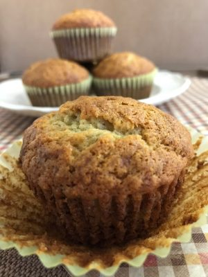 A banana muffin sitting on top of the wrapper with 3 more muffins in the background.