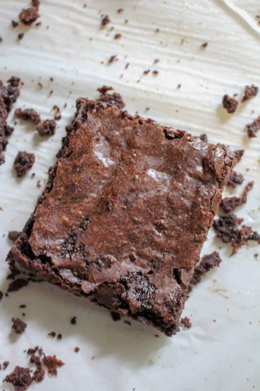 A double chocolate brownie with crumbs on a wooden counter.
