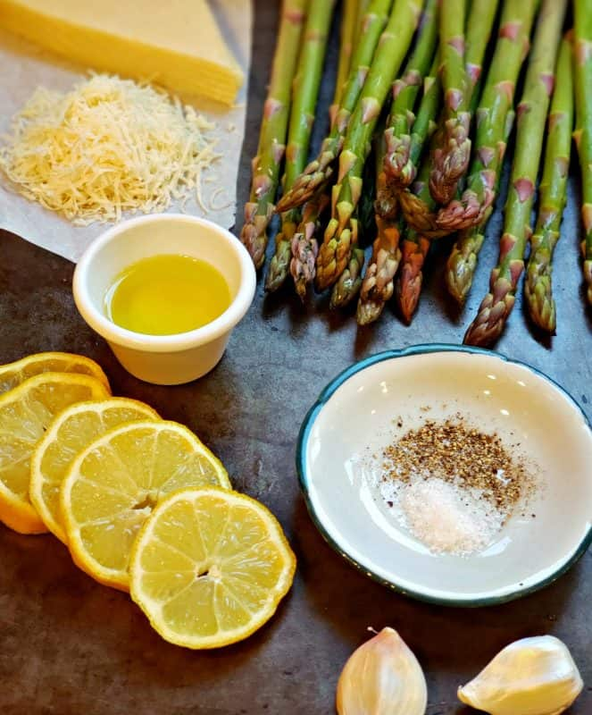 Butter, Parmesan cheese, asparagus spears and lemon slices laid out for the ingredients for baked lemon asparagus.
