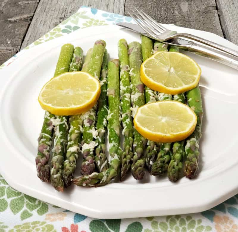 Lemon asparagus on a white plate topped with fresh lemon slices.