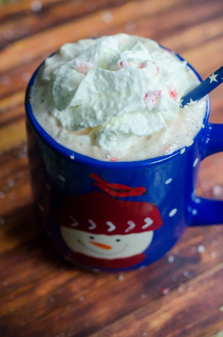 Homemade peppermint hot chocolate in a blue mug with a snowman on it.
