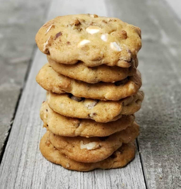 Triple Chunk Pecan Cookies stacked on a wooden background