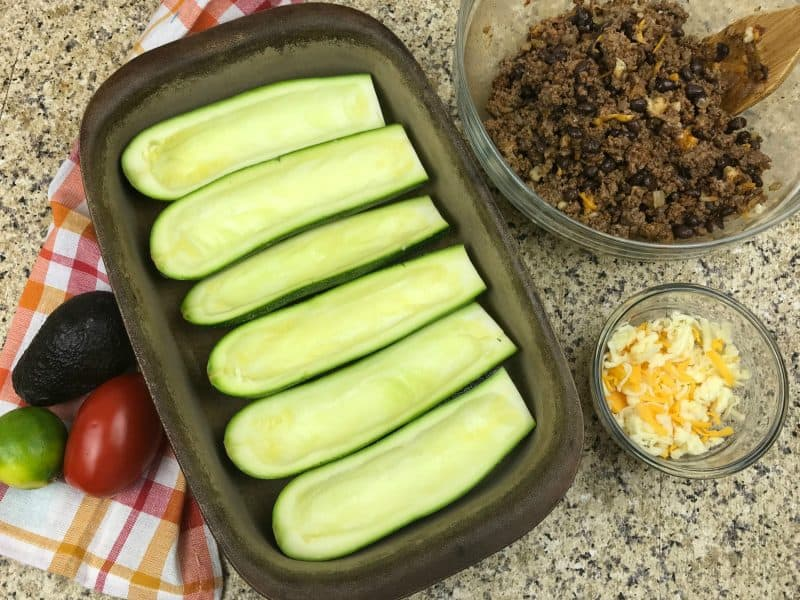 Hollowed out zucchini on a baking sheet with taco meat and cheese in bowls on the side.
