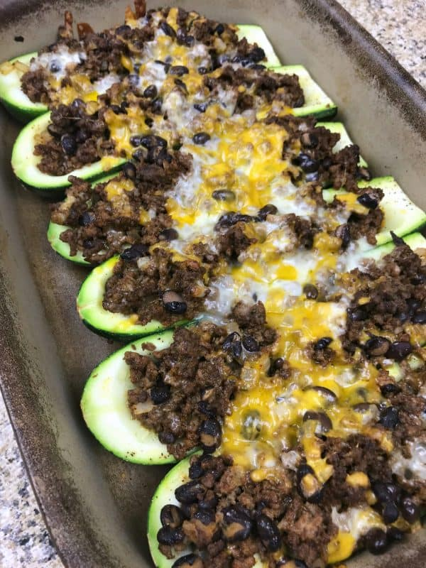 Zucchini taco boats on a baking sheet, topped with cheese.