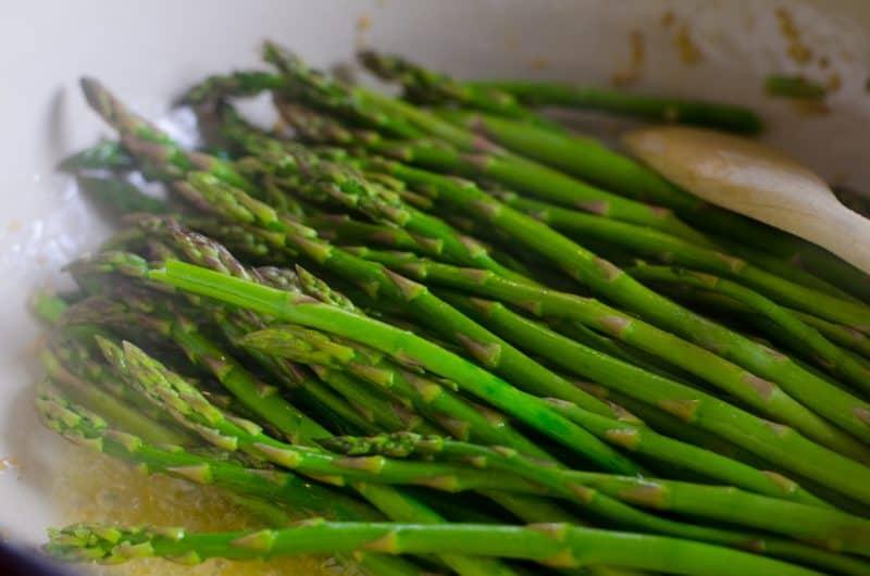 Steamed asparagus sprinkled with seas salt in a pan.