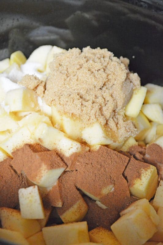 Diced seasoned apples in a slow cooker to make apple butter.