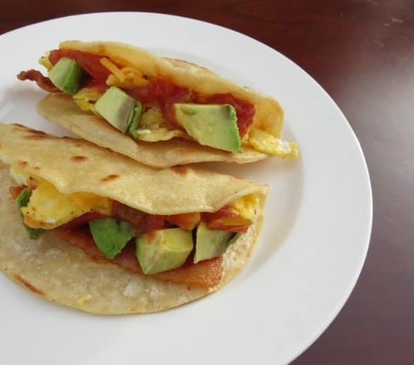 Breakfast tacos with bacon and avocado in a corn tortilla shell.